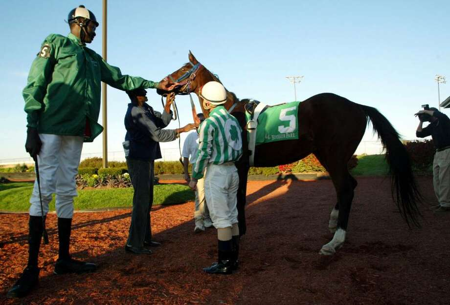 ANDERSON, IN - OCTOBER 18:  Former NBA star Manute Bol reaches out to touch Alpena Magic, a two-year-old thoroughbred at Hoosier Park October 18, 2003 in Anderson, Indiana. Bol, who played 11 seasons in the NBA and was the tallest man in professional basketball at 7-foot-7, appeared at the thoroughbred racing track north of Indianapolis as part of a charity effort to raise money for refugees in his native Sudan. Bol became the tallest jockey ever licensed by the Indiana Horse Racing Commission.  (Photo by Brent Smith/Getty Images) Photo: Brent Smith, Getty Images / 2003 Getty Images