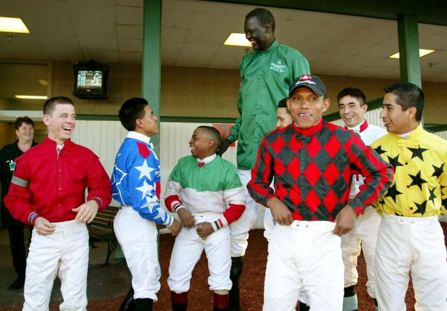 ANDERSON, IN - OCTOBER 18:  Former NBA star Manute Bol (at back in green) shares a laugh with jockeys from Hoosier Park October 18, 2003 in Anderson, Indiana. Bol, who played 11 seasons in the NBA and was the tallest man in professional basketball at 7-foot-7, appeared at the thoroughbred racing track north of Indianapolis as part of a charity effort to raise money for refugees in his native Sudan. Bol became the tallest jockey ever licensed by the Indiana Horse Racing Commission.  (Photo by Brent Smith/Getty Images) Photo: Brent Smith, Getty Images / 2003 Getty Images