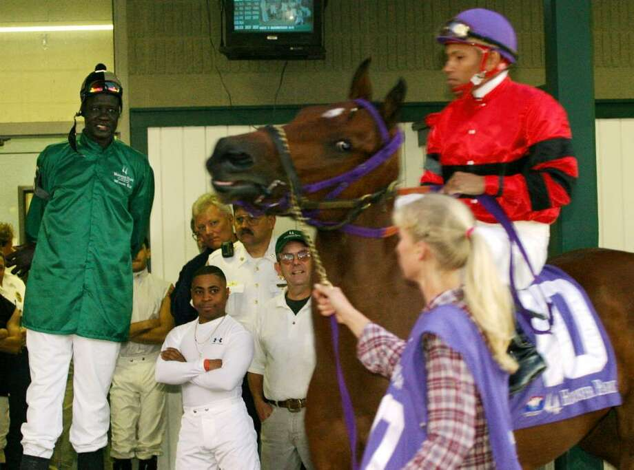 ANDERSON, IN - OCTOBER 18:  Former NBA star Manute Bol (L) watches a horse and jockey pass him before a race at Hoosier Park October 18, 2003 in Anderson, Indiana. Bol, who played 11 seasons in the NBA and was the tallest man in professional basketball at 7-foot-7, appeared at the thoroughbred racing track north of Indianapolis as part of a charity effort to raise money for refugees in his native Sudan. Bol became the tallest jockey ever licensed by the Indiana Horse Racing Commission.  (Photo by Brent Smith/Getty Images) Photo: Brent Smith, Getty Images / 2003 Getty Images