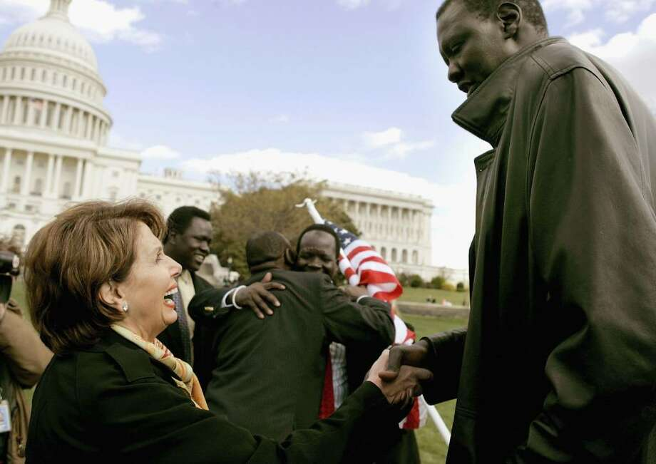 WASHINGTON - APRIL 05:  House Minority Leader Nancy Pelosi (L) shakes hands with 7-foot 6 inch tall Manute Bol during a rally April 5, 2006 in Washington DC. The rally was held to shed light on the genocide and modern-day slavery in Sudan.  (Photo by Mark Wilson/Getty Images) Photo: Mark Wilson, Getty Images / 2006 Getty Images