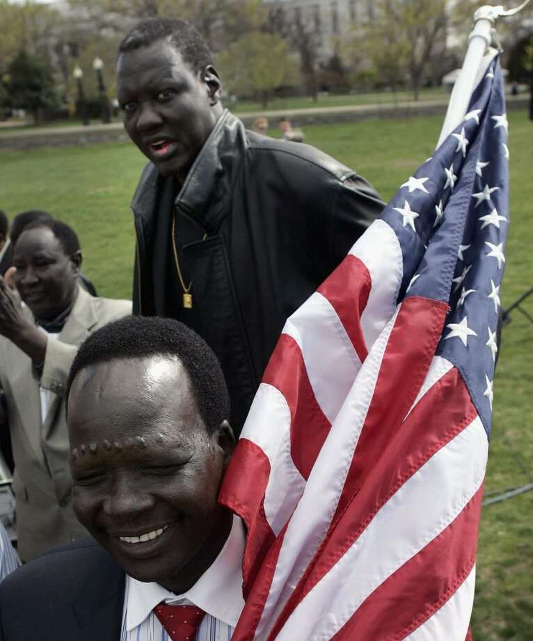 WASHINGTON - APRIL 05: Former Sudanese slave Simon Deng (L) and 7-foot 6-Inch Manute Bol attend a rally after Deng completed a 300 mile walk from New York to Washington  April 5, 2006 in Washington DC. The rally was held to shed light on the genocide and modern-day slavery in Sudan.  (Photo by Mark Wilson/Getty Images) Photo: Mark Wilson, Getty Images / 2006 Getty Images