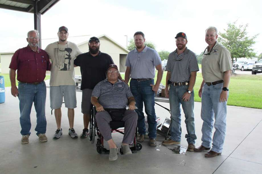 Larry Hinkle, third from the left, is walking across Texas to honor war veterans and first responders. He visited with Tomball veterans and first responders at a lunch on Monday with Steve Peltier, left, Chad Foran, Steve Vaughan, in the foreground, Jacob Peltier, Kyle Hope and Jeremy Peltier. Photo: Mayra Cruz