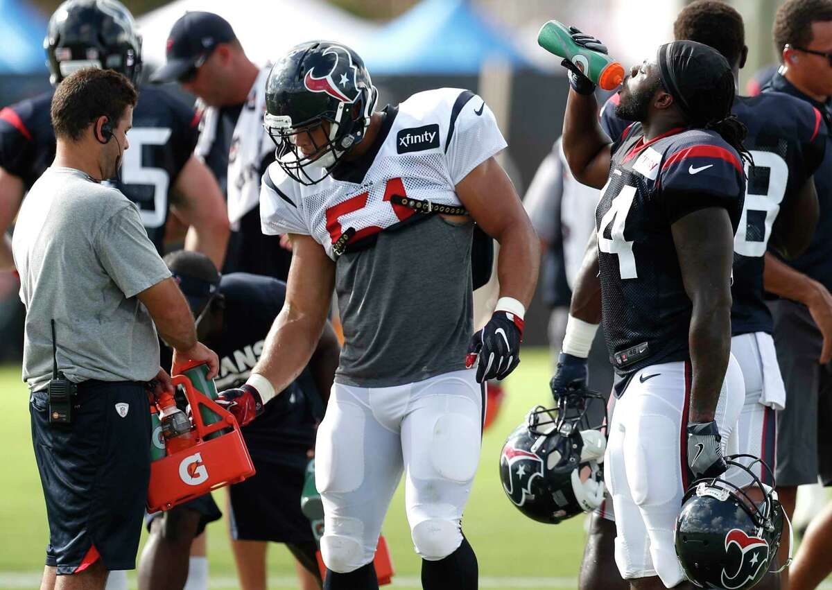 Houston Texans linebacker Dylan Cole (51) and running back Dare Ogunbowale (44) drink water during a break in practice during training camp at The Methodist Training Center on Tuesday, Aug. 22, 2017, in Houston.