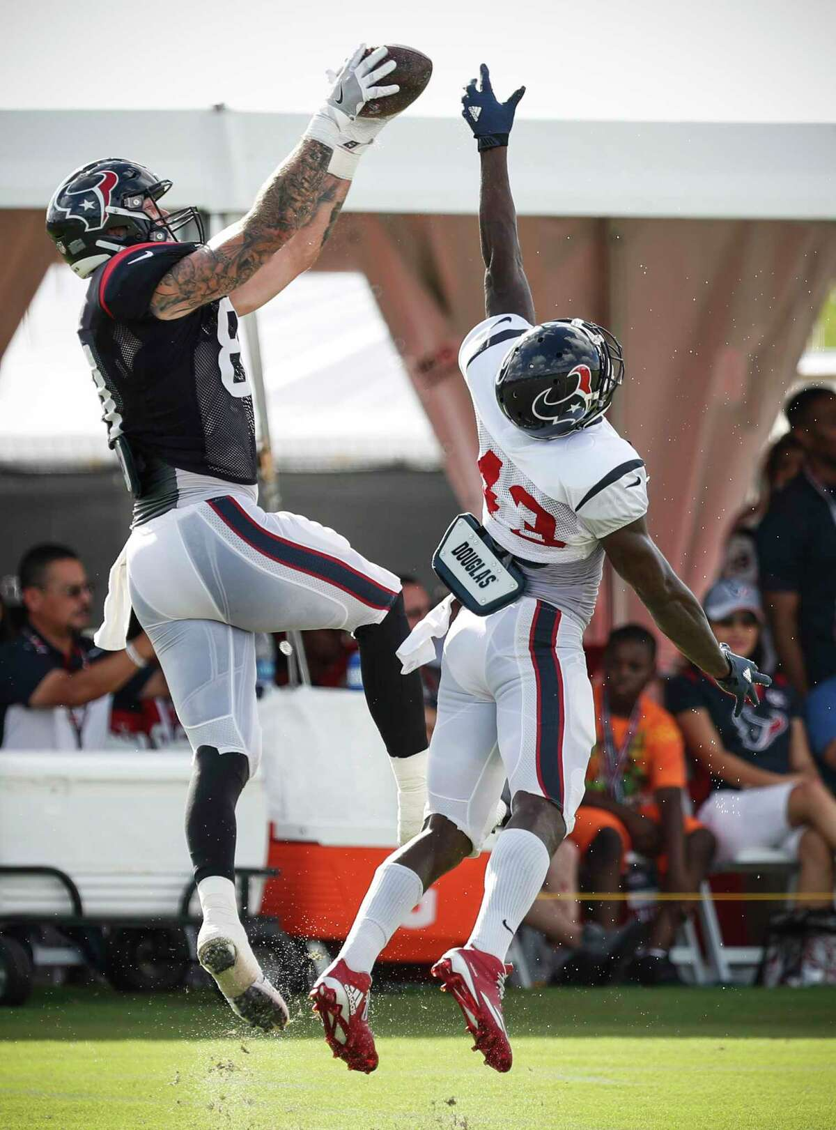 Houston Texans tight end Evan Baylis (81) goes up over strong safety Corey Moore (43) to make a catch during training camp at The Methodist Training Center on Tuesday, Aug. 22, 2017, in Houston.