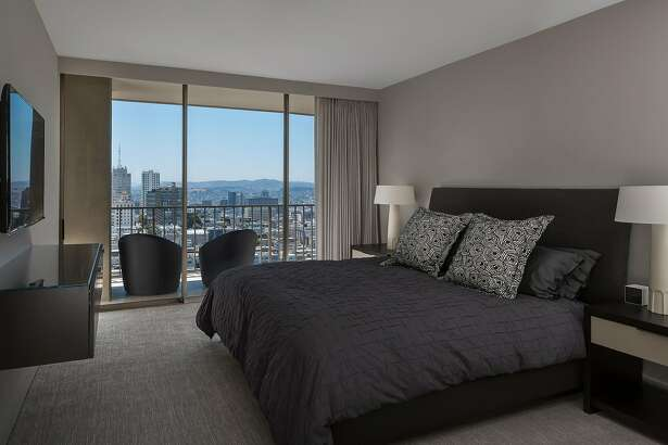 The carpeted master suite enjoys built-ins and city views.