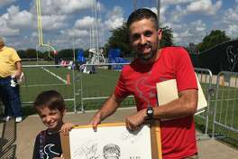 Terry Harman and his son show off his J.J. Watt pencil drawing that he got Watt to autograph after Monday's Houston Texans practice.