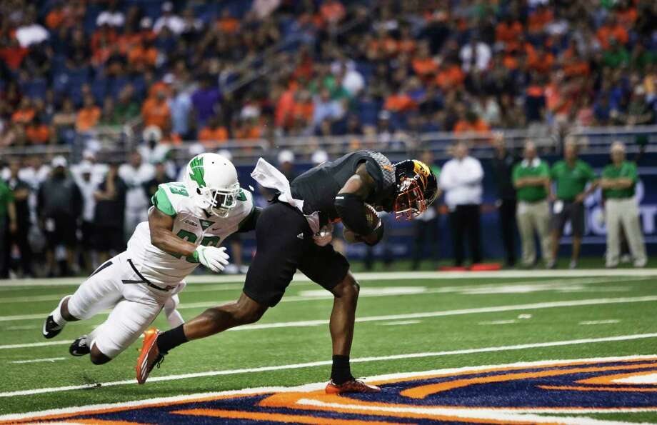UTSA's Kerry Thomas Jr. scores a first half touchdown as North Texas' Kishawn McClain during the game between the UTSA Roadrunners and the North Texas Mean Green at the Alamodome in San Antonio, Texas on Saturday, October 29, 2016. Photo: Matthew Busch, For The San Antonio Express-News / © Matthew Busch