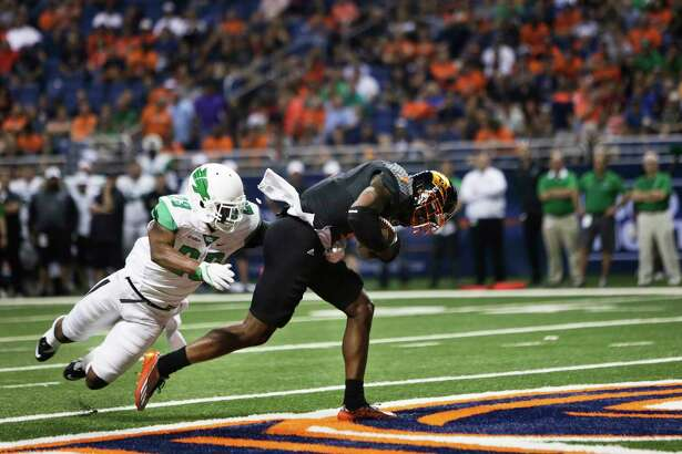 UTSA's Kerry Thomas Jr. scores a first half touchdown as North Texas' Kishawn McClain during the game between the UTSA Roadrunners and the North Texas Mean Green at the Alamodome in San Antonio, Texas on Saturday, October 29, 2016.