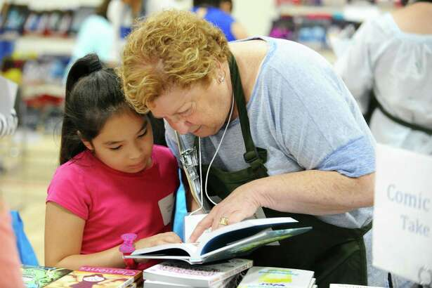A rising first grader and her volunteer shopper read through a book before selecting it during the annual Back to School Shop, which benefits children entering first grade, inside Davenport Ridge Elementary School in Stamford, Conn. on Sunday, July 30, 2017.