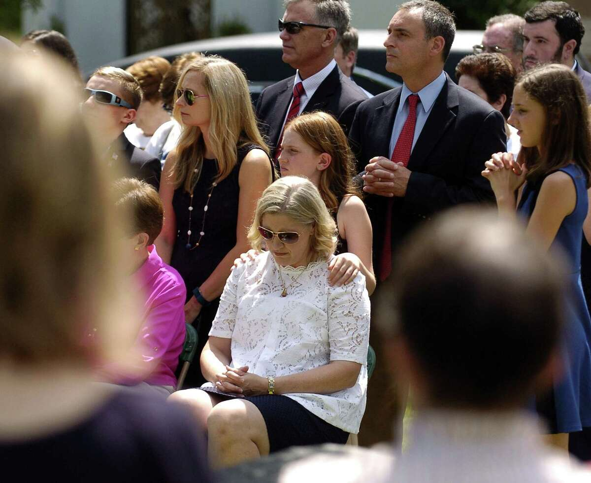 """Madeline Galgano places her hand on the shoulder of her mother, Anmarie Galgano, as they attend a Military honors burial for Galgano's Uncle, Patrick J. Byrnes, known as """"Bud,"""" at Queen of Peace Cemetery on Saturday, August 19, 2017 in Stamford, Connecticut. Byrnes was killed in action in 1943 at the age of 23. His remains were recently identified by the U.S. Army and returned to his family."""