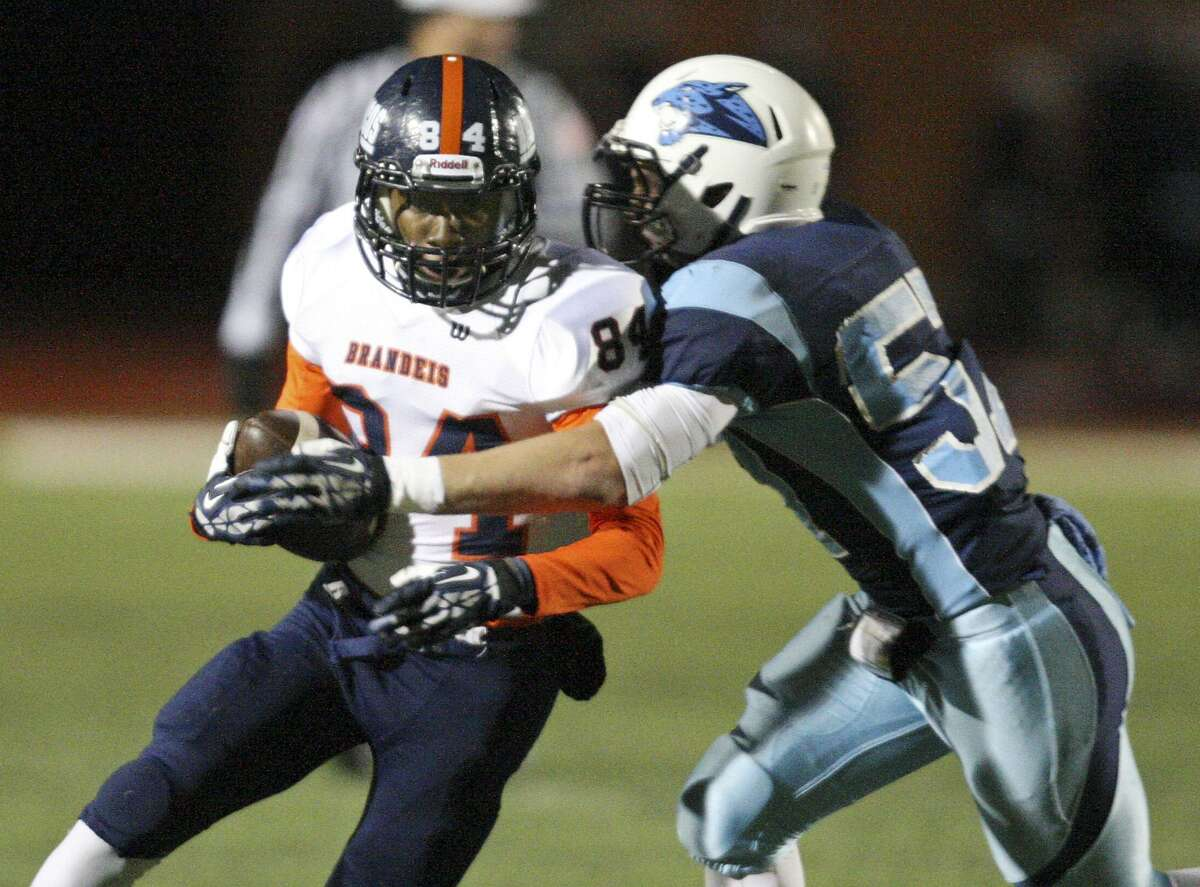 Brandeis' Larry Stephens looks for room around Johnson's Kyle Lollar during first half action of their Class 5A Division II area playoff game on Nov. 22, 2013 at Heroes Stadium.