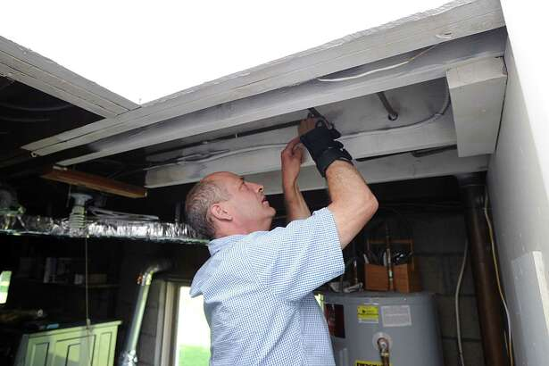 David Thomas demonstrates how to test for lead by scraping metal from the water pipes in the basement of his home in Darien, Conn., Tuesday, June 27, 2017. Thomas owns a lead pipe testing company.