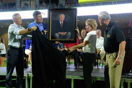 Michael Oulette, Executive Director of Fine Arts (Left), Lance Hindt, Katy ISD Superintendent and Debbie Decker, Executive Director of Athletics, unveil a portrait of Mike Johnson at the dedication ceremony for Katy ISD's Mike Johnson Field and Legacy Stadium in Katy, TX on August 17, 2017.