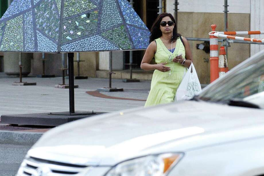 Shilpa Dev, 29, of Stamford listens to music on her cell phone as she crosses Broad Street on Wednesday, August 16, 2017 in Stamford, Connecticut. Photo: Matthew Brown / Hearst Connecticut Media / Stamford Advocate