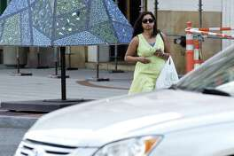 Shilpa Dev, 29, of Stamford listens to music on her cell phone as she crosses Broad Street on Wednesday, August 16, 2017 in Stamford, Connecticut.