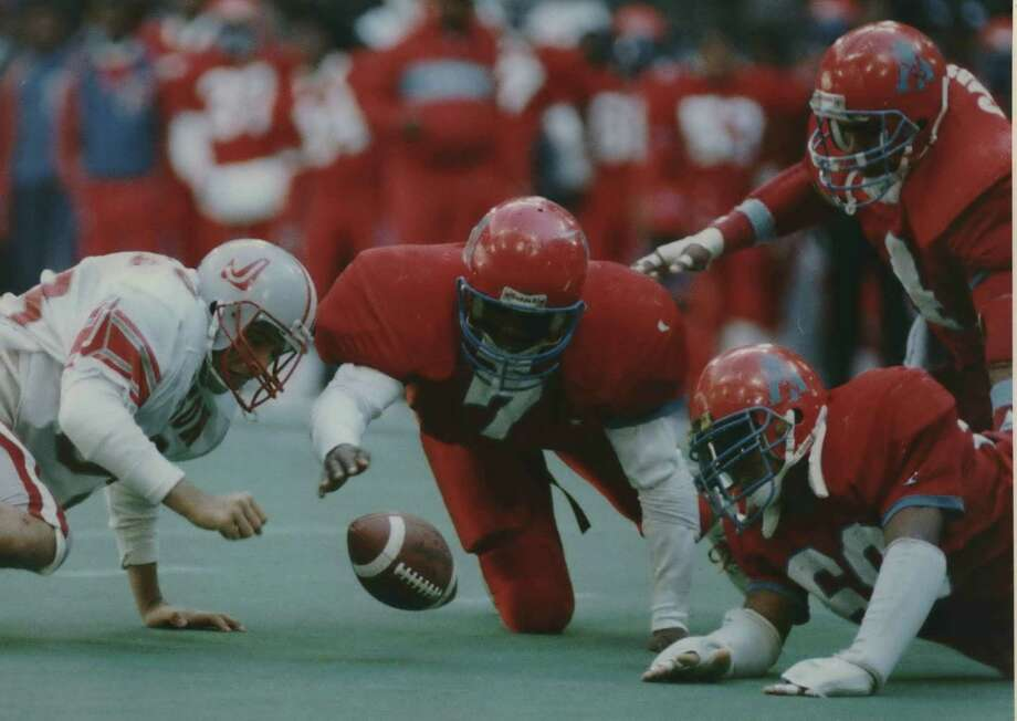 Judson's Luis Silva (left) and Dallas Carter's Leshai Maston (7) and Jeffrey McInnis (on ground) scramble for a fumble during the Class 5A state championship game on Dec. 17, 1988, at Texas Stadium in Irving. Judson lost 31-14, but later earned the title when Carter forfeited because of the use of an ineligble player. Photo: Express-News File Photo / San Antonio Express-News