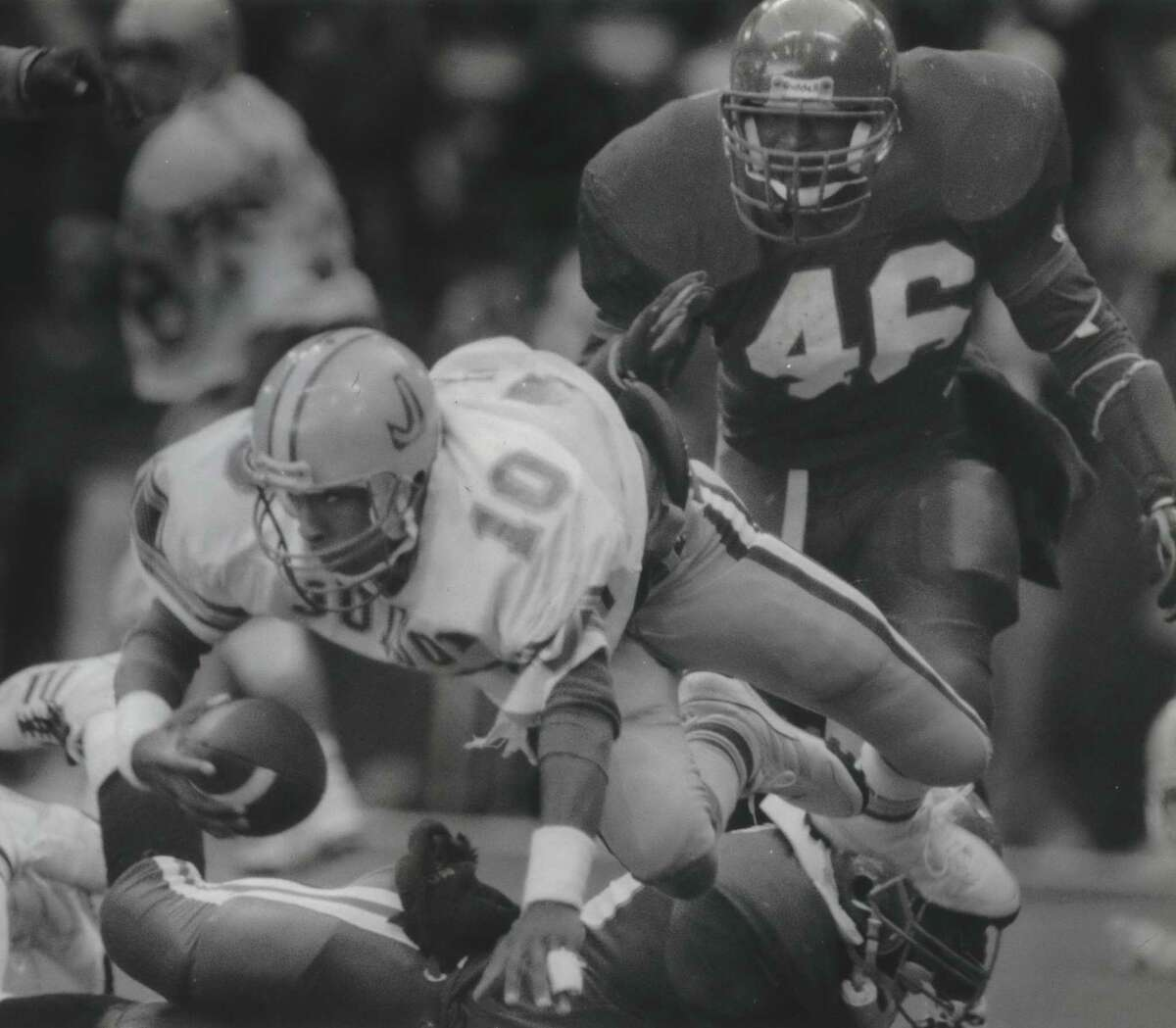Judson quarterback Mike Jinks (10) dives for an extra yard as Dallas Carter's Jesse Armstead (46) pursues during the 1988 Class 5A state championship game at Texas Stadium in Irving