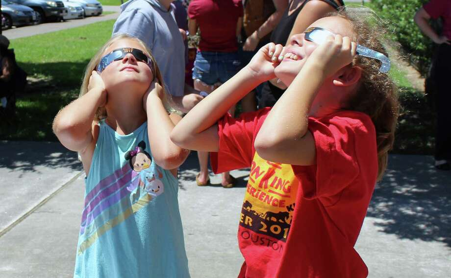 Anna and Abby Ellisor use eclipse glasses to look at the partial eclipse during the eclipse viewing party at Harris County Public Library Crosby-Edith Fae Cook Cole Branch in Crosby on Monday, Aug. 21. Photo: Melanie Feuk