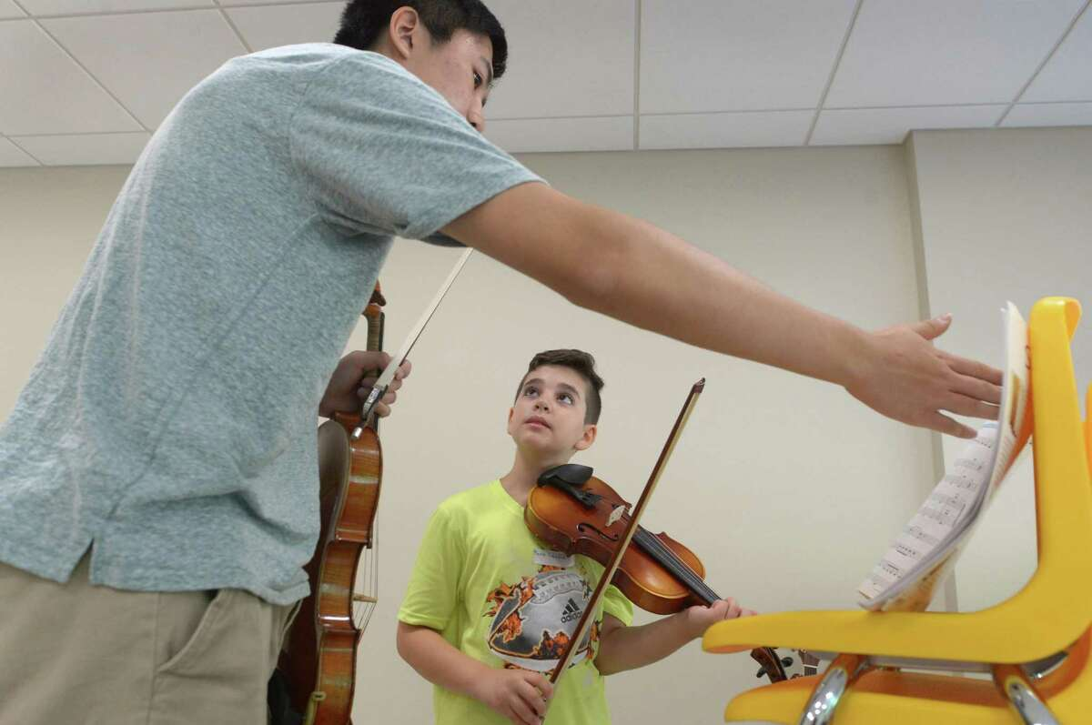 Daniel Cui teaches Mario Cavone, 10, violin during the Wilton Roots of Music summer camp at the Comstock Community Center Tuesday, Aug. 22, in Wilton. The student-run, nonprofit camp Roots of Music was established by Isabella Palacpac, a current student at the Juilliard School of Music and offers instruction for students from kindergarten to fifth-grade. The camp also teaches students sight-reading, rhythm, choir arts, and acting/theater.
