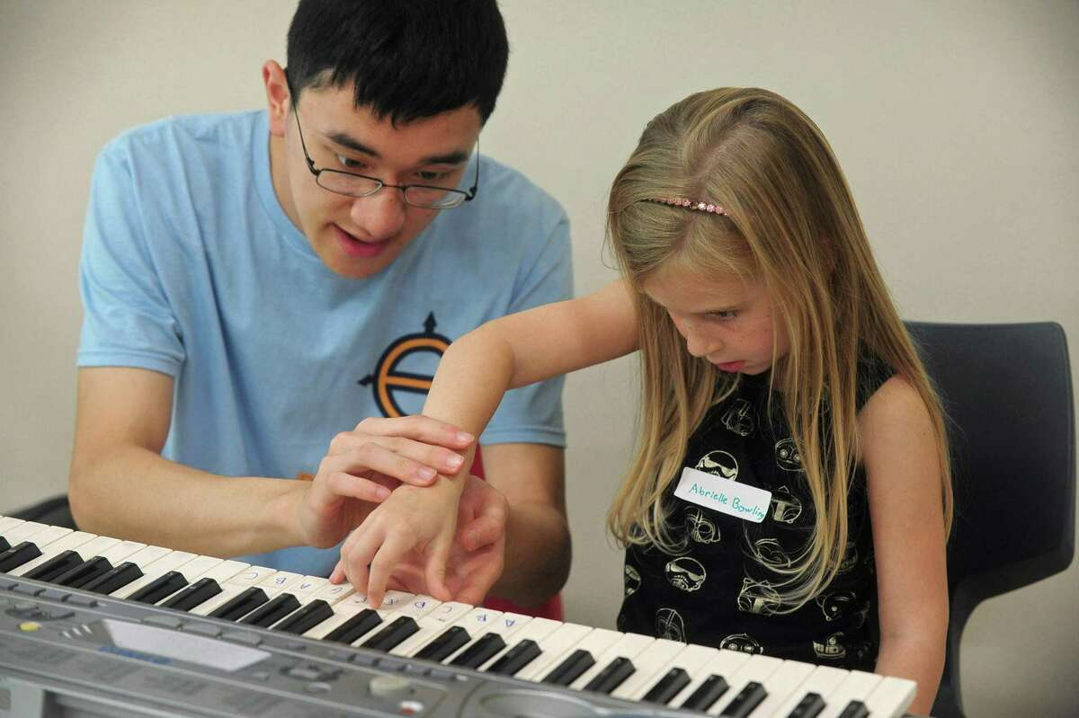 President of Wilton Roots of Music summer camp, Albert Wei, teaches Abrielle Bowling, 6, piano during the camp at the Comstock Community Center Tuesday, Aug. 22, in Wilton. The student-run, nonprofit camp Roots of Music was established by Isabella Palacpac, a current student at the Juilliard School of Music and offers instruction for students from kindergarten to fifth-grade. The camp also teaches students sight-reading, rhythm, choir arts, and acting/theater.