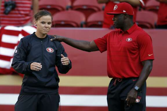 San Francisco 49ers assistant coach Katie Sowers, left, talks with a fellow coach before a preseason NFL football game against the Denver Broncos Saturday, Aug. 19, 2017, in Santa Clara, Calif. (AP Photo/D. Ross Cameron)
