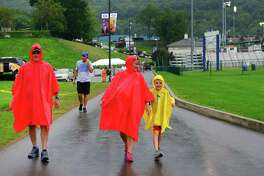 A family wears ponchos as rain moves through the grounds at the Little League Baseball World Series in South Williamsport, Penn., on Tuesday Aug. 22, 2017.