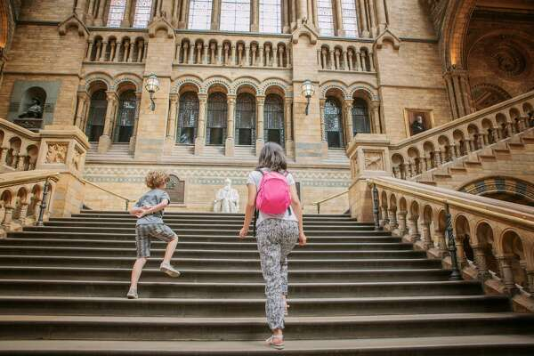tourist kids in main hall of history natural museum in London.The Natural History Museum was built in 1881 to house the British Museum's growing collection of natural history specimens. The vast building is a masterpiece
