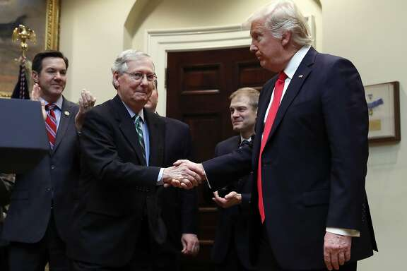 FILE - In this Feb. 16, 2017, file photo, President Donald Trump shakes hands with Senate Majority Leader Mitch McConnell of Ky., during a ceremony in the Roosevelt Room of the White House in Washington. Trump�s attacks on McConnell come at the worst possible time, if the president�s goal is actually to accomplish the agenda on health care, infrastructure and taxes he�s goading his GOP ally to pass. Behind from left are Rep. Evan Jenkins, R-W.Va., and Rep. Jim Jordan, R-Ohio.(AP Photo/Carolyn Kaster, File)