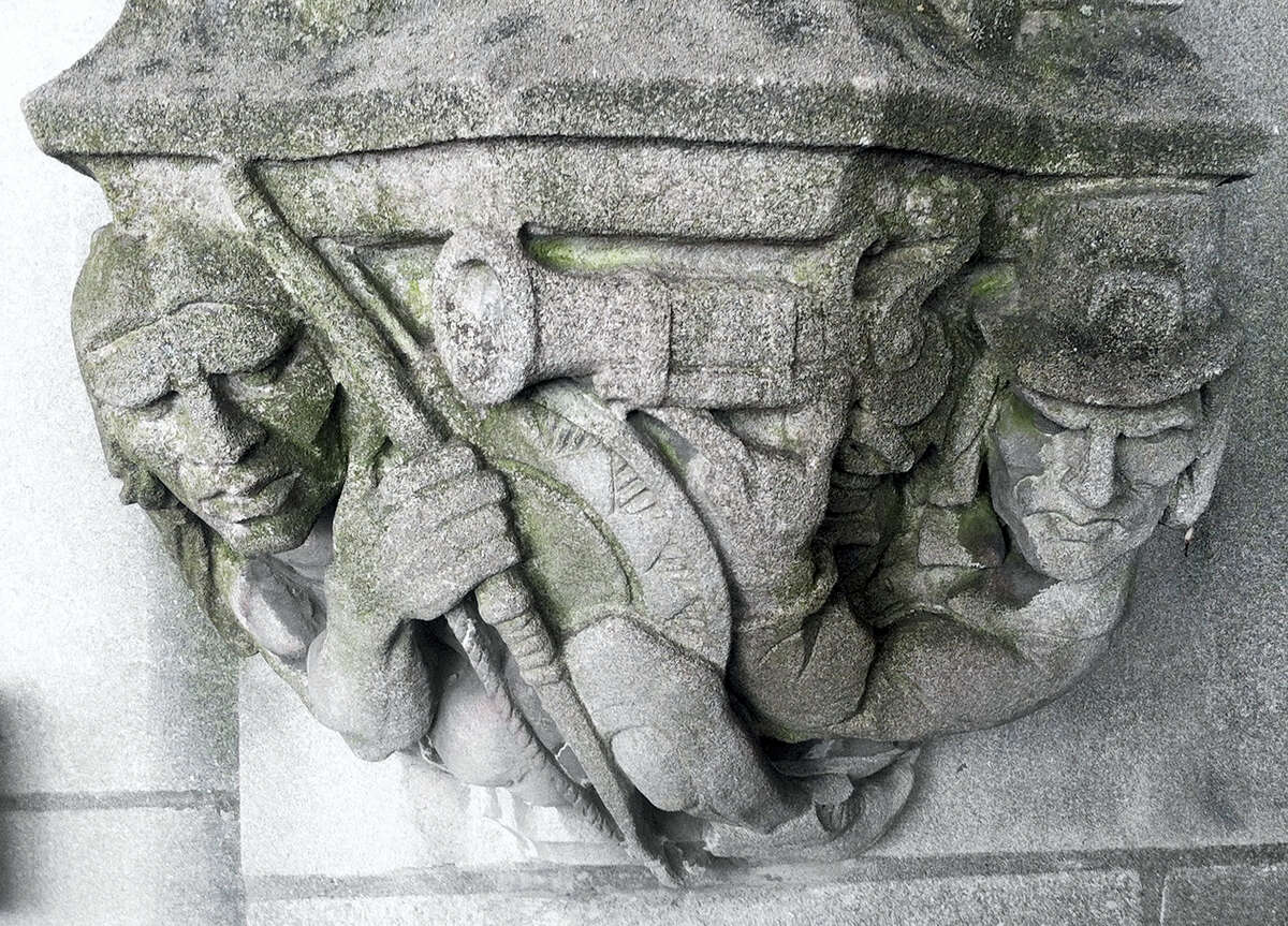 A 1929 doorway carving depicts a Puritan settler, right, pointing a musket at the head of a Native American, left, on the school's campus in New Haven.