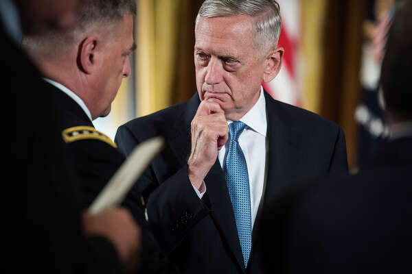 Defense Secretary James Mattis, right, talks with Chief of Staff of the Army Gen. Mark Milley, left, before President Donald Trump bestows the Medal of Honor on retired Army medic James McCloughan at a White House ceremony on July 31.