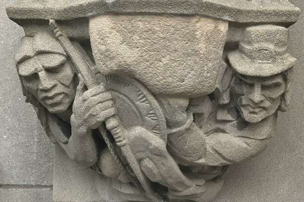 """In this July 20, 2017 photo provided by Yale University, a 1929 doorway carving on the school's New Haven, Conn., campus depicts a Puritan settler, right, with a musket pointing at the head of a Native American, left, which had been covered by workers with removable stone when the seldom-used doorway was converted into a main entrance. A Yale committee charged with assessing potentially offensive art decided to remove it, but will make it available for public display elsewhere so as to not destroy """"reminders of unpleasant history."""" (Yale University via AP)"""
