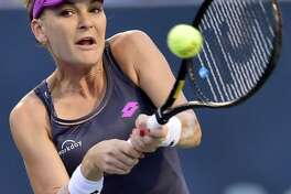 Top seed Agnieska Radwanska of Poland returns a volley against Eugenie Bouchard during her 6-3, 7-5 win at the Connecticut Tennis Center in New Haven.