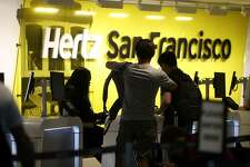SAN FRANCISCO, CA - AUGUST 08: Customers are assisted at a Hertz rental car office on August 8, 2017 in San Francisco, California. Rental car companies are seeing a drop in earnings and stock prices as they struggle to deal with large inventories and competition from ridesharing companies Uber and Lyft. Avis had initially forecast annual profits of $3.50 a share but recently had to change that forecast to $2.40 to $2.85 a share. (Photo by Justin Sullivan/Getty Images)