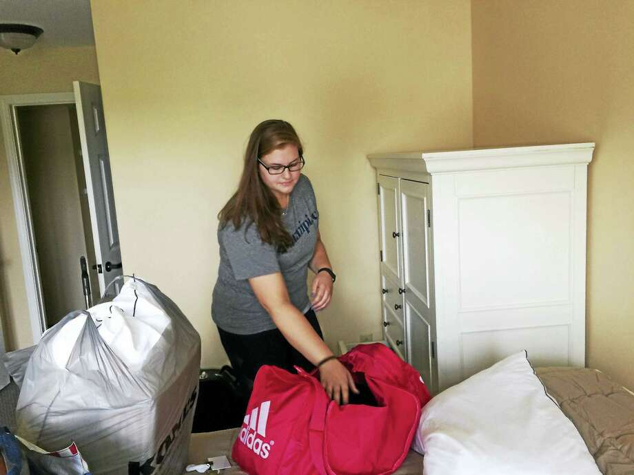 "Sarah Cullen, a Quinnipiac University junior majoring in occupational therapy, unpacks in her apartment at Masonicare'e Ashlar Village Tuesday. Cullen is participating in the ""Students-In-Residence"" program and will be living with senior citizens who are part of Ashlar Village's assisted living community. Photo: Luther Turmelle / Hearst Connecticut Media"