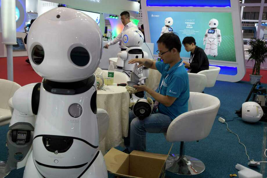 A worker repairs the arm of a robot this week before the opening of the World Robot Conference in Beijing. The annual conference is a showcase of China's burgeoning robot industry. Photo: Ng Han Guan, STF / Copyright 2017 The Associated Press. All rights reserved.