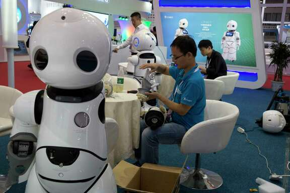 A worker repairs the arm of a robot this week before the opening of the World Robot Conference in Beijing. The annual conference is a showcase of China's burgeoning robot industry.