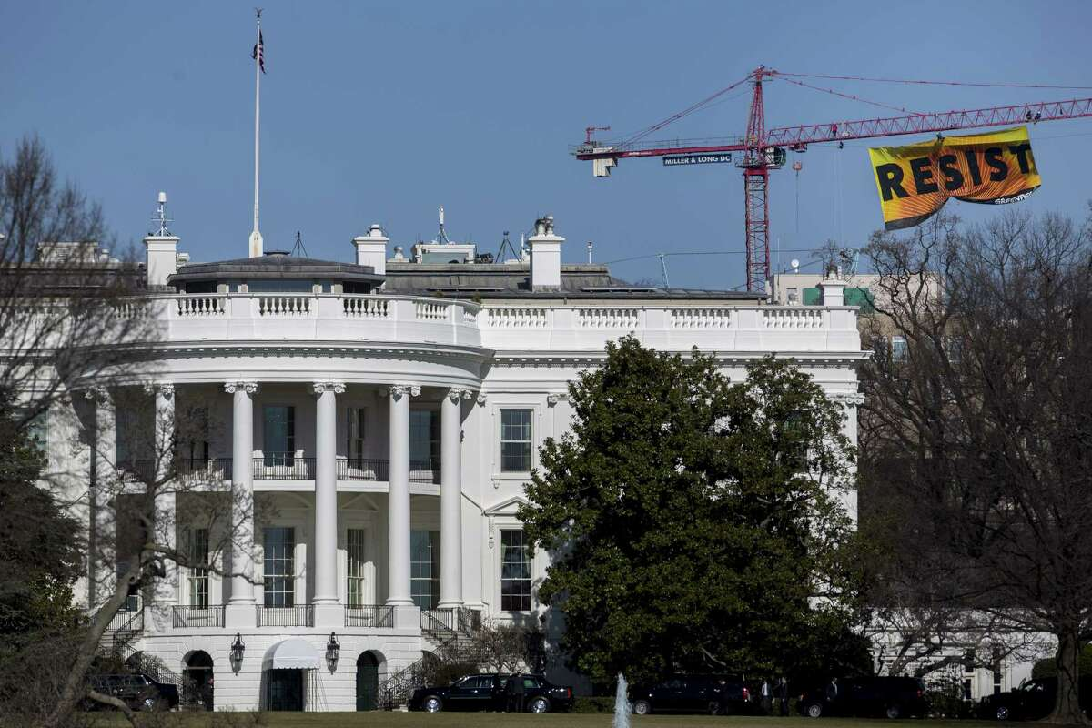 """Greenpeace activists hang a banner off of a construction crane that reads """"Resist"""" past the White House in Washington, D.C., U.S., on Wednesday, Jan. 25, 2017. The protest comes one day after the Trump administration invited TransCanada Corp. to reapply for its Keystone XL project and issued a memorandum supporting completion of the Energy Transfer Partners LPs Dakota Access Pipeline. Photographer: Andrew Harrer/Bloomberg"""