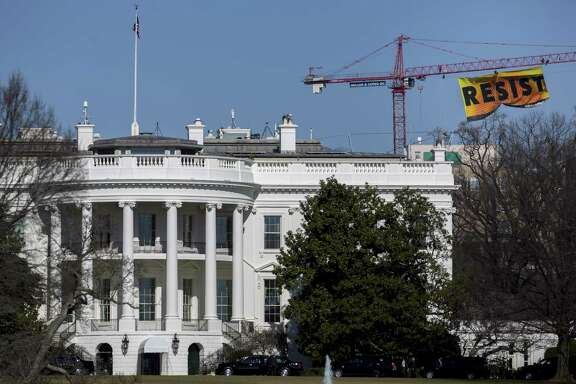 "Greenpeace activists hang a banner off of a construction crane that reads ""Resist"" past the White House in Washington, D.C., U.S., on Wednesday, Jan. 25, 2017. The protest comes one day after the Trump administration invited TransCanada Corp. to reapply for its Keystone XL project and issued a memorandum supporting completion of the Energy Transfer Partners LPs Dakota Access Pipeline. Photographer: Andrew Harrer/Bloomberg"