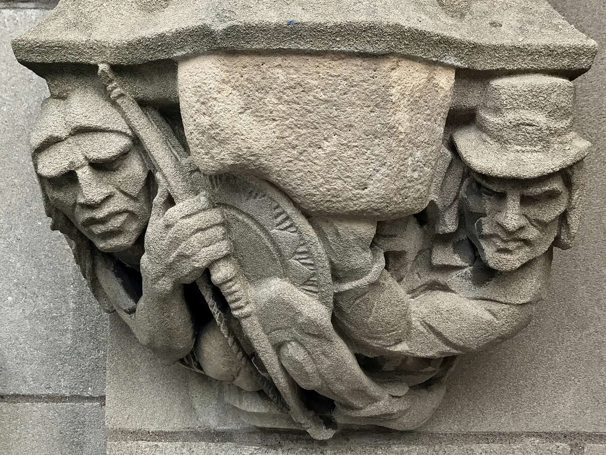A 1929 doorway carving depicts a Puritan settler, right, pointing a musket at the head of a Native American, left, on the school's campus in New Haven, but the musket has been covered over by the university.