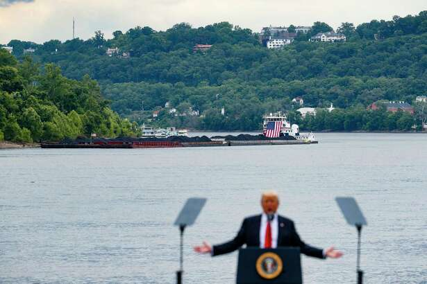 FILE - In this June 7, 2017 file photo, a coal barge is positioned as a backdrop behind President Donald Trump as he speaks during a rally at the Rivertowne Marina in Cincinnati. President Donald Trump personally promised to activate emergency legal authorities to keep dirty or economically uncompetitive coal plants from shutting down, a top American coal company said. The Trump administration now says it has no plans to do so.  (AP Photo/John Minchillo, File)