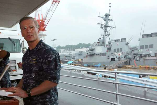 Vice Adm. Joseph Aucoin, Commander of the U.S. 7th Fleet, speaks during a press conference with the damaged USS Fitzgerald as background at the U.S. Naval base in Yokosuka, southwest of Tokyo Sunday, June 18, 2017.  The U.S. destroyer Fitzgerald collided with a container ship in the busy sea off Japan, Saturday. (AP Photo/Eugene Hoshiko)
