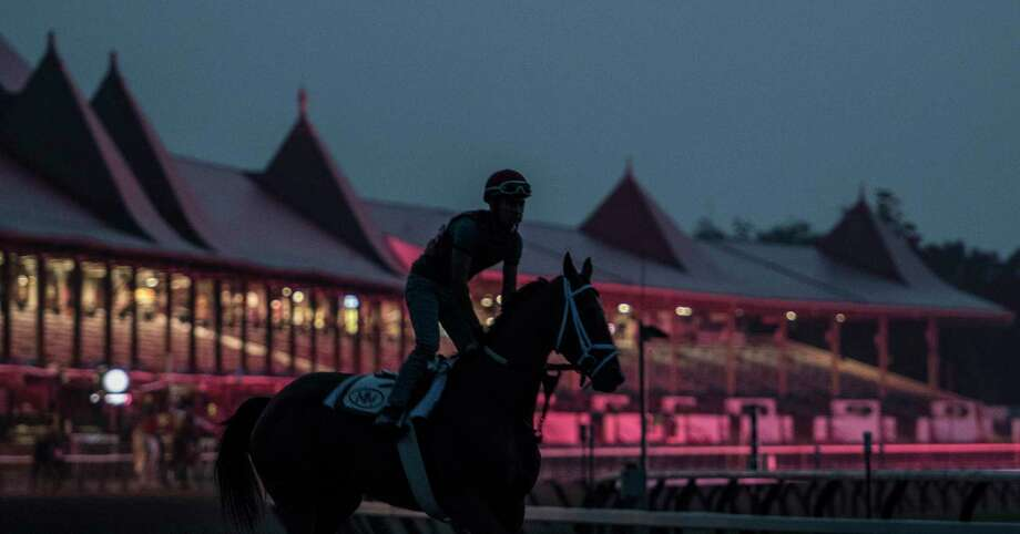 Horses work before dawn at the Saratoga Race Course in the reflection of the infield tote board Tuesday Aug. 22, 2017 in Saratoga Springs, N.Y.  (Skip Dickstein/Times Union) Photo: SKIP DICKSTEIN