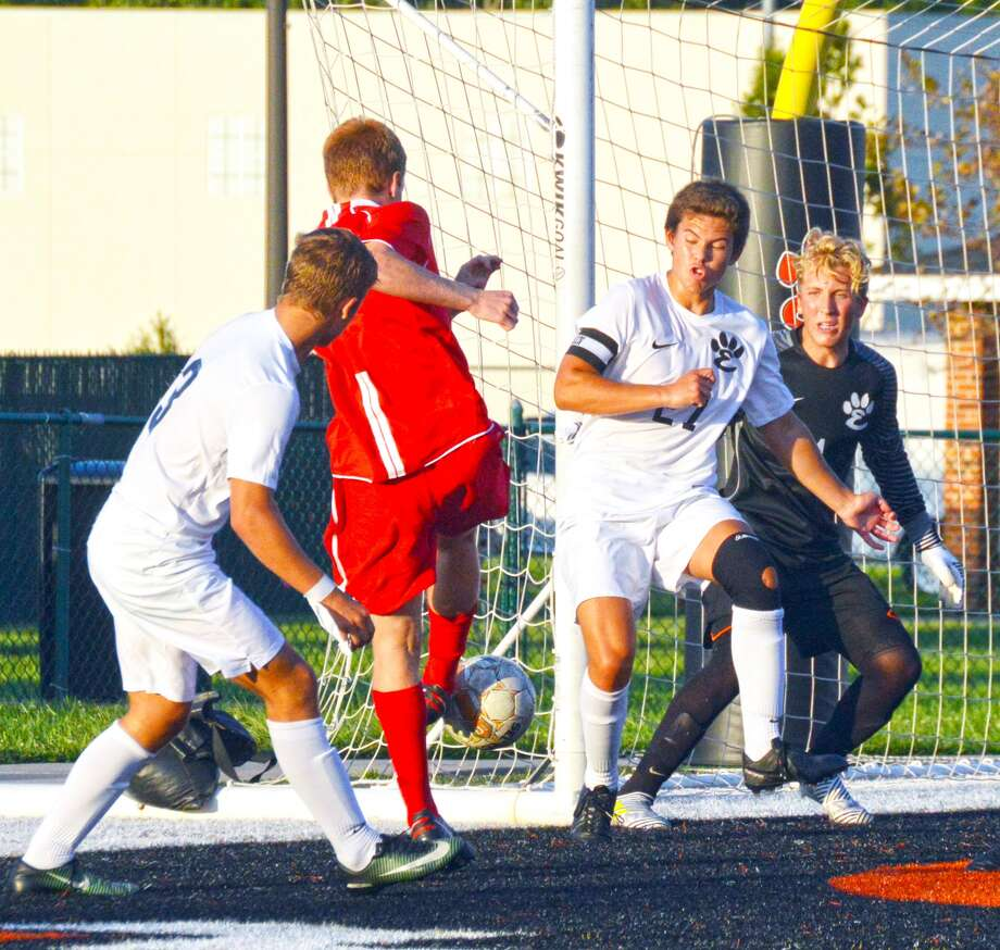 Edwardsville's Kadin Lieberman, left, Zach Timmermann, center, and keeper Michael Hoelting keep the ball out of the net.