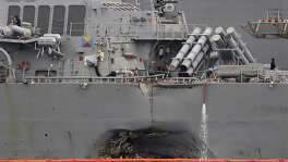 The damaged port aft hull of the USS John S. McCain, is visible while docked at Singapore's Changi naval base.