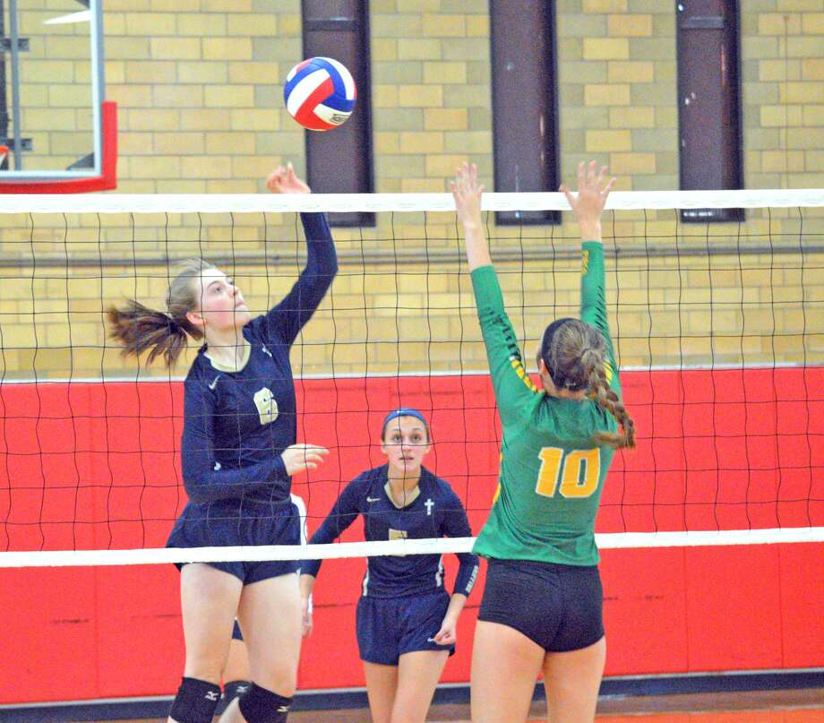 Father McGivney junior Emma Deist, left, goes up for a kill during Tuesday's match against Piasa  Southwestern at the Roxana Tournament.