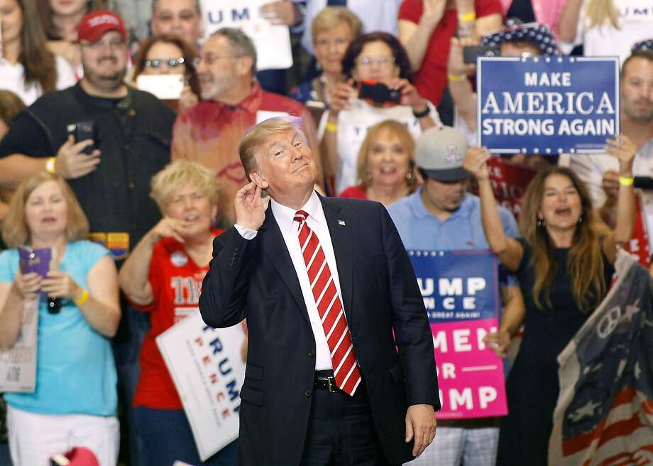 President Donald Trump gestures during a rally at the Phoenix Convention Center on August 22, 2017 in Phoenix, Arizona. An earlier statement by the president that he was considering a pardon for Joe Arpaio,, the former sheriff of Maricopa County who was convicted of criminal contempt of court for defying a court order in a case involving racial profiling, has angered Latinos and immigrant rights advocates.  Photo: Ralph Freso, Getty Images