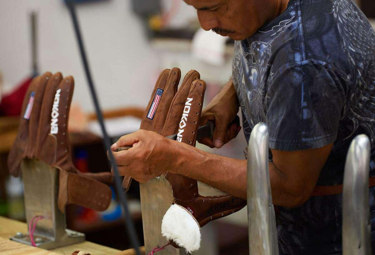 An employee shapes a ball glove on hot steel fingers at the Nokona manufacturing facility in Nocona in July. (