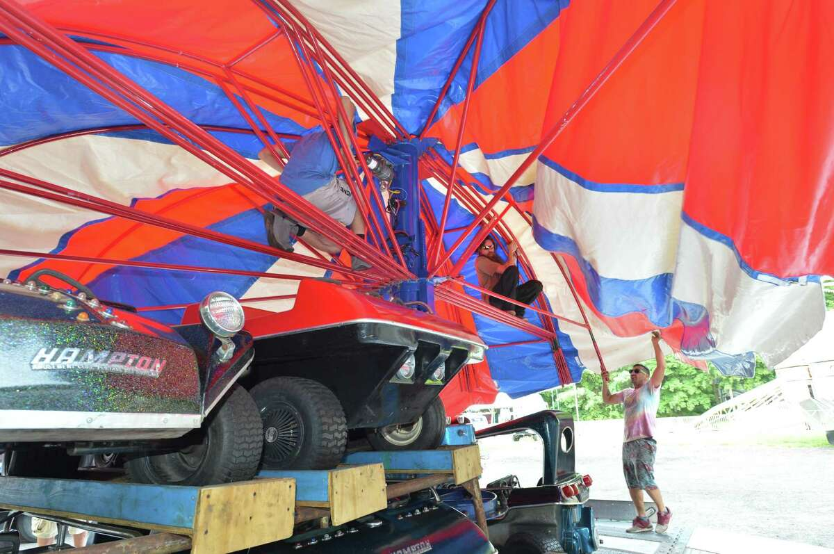 Fred Gallipoli with Savin Rock Amusements pulls the cover over the Hampton Buggy ride while setting up on Tuesday for the Norwalk Greek Festival at St. George Greek Orthodox Church .The festival features authentic homemade Greek cuisine, traditional dancing, games rides and vendors. It starts at 5 p.m. on Thursday . Admission is free.