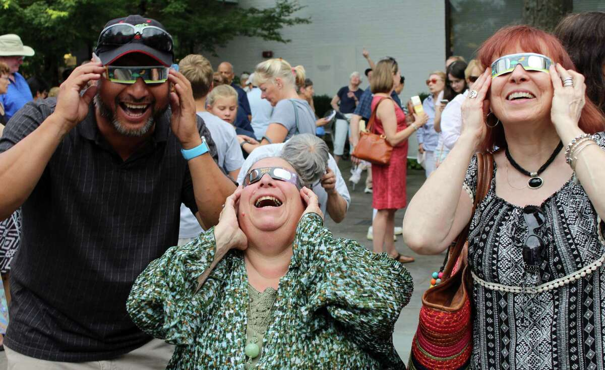 Eduardo Zunmata, of Peru, Susan Bettigole, of Milford, and Kathy Hall, of West Haven, view the solar eclipse at Wilton Library on Monday, Aug. 21, 2017.