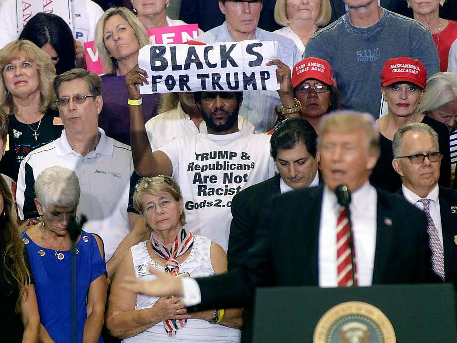 A supporter of President Donald Trump holds up a sign as the president speaks to a crowd at the Phoenix Convention Center during a rally on August 22, 2017 in Phoenix, Arizona. Photo: Ralph Freso, Getty Images